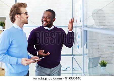 Confident male colleagues discussing statistic data in office