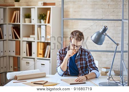 Young architect making sketches at workplace