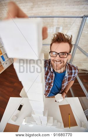 Young designer or architect putting cube on top of high pyramid