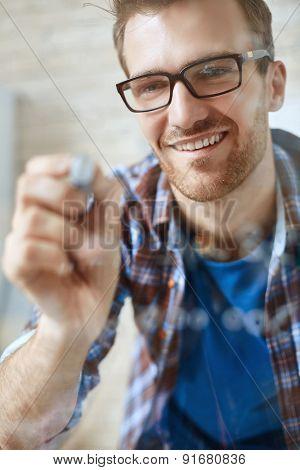 Smiling businessman in eyeglasses making notes on transparent board