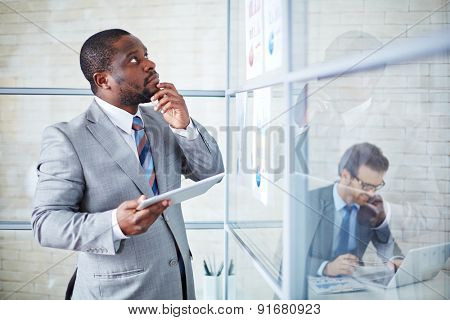 Pensive businessman with touchpad looking at documents in office