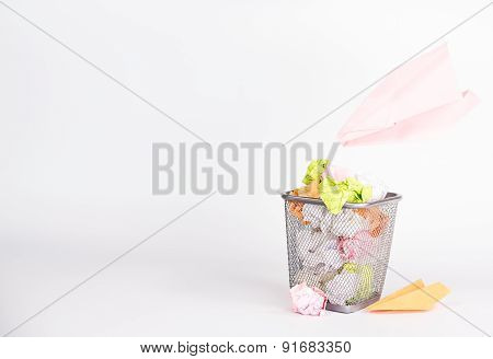 isolated wastebasket full of color waste paper and paper airplane
