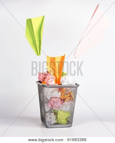 isolated wastebasket full of color waste paper and paper airplanes