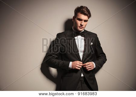 Elegant young business man closing his jacket while leaning on a wall.