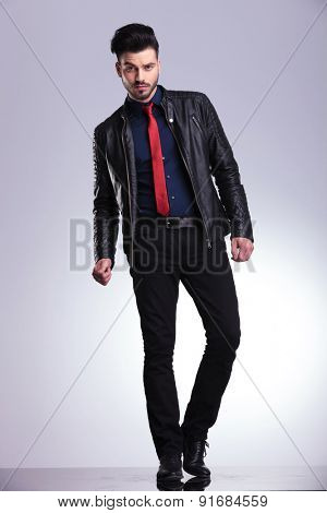 Full body picture of a young business man standing on grey studio background.