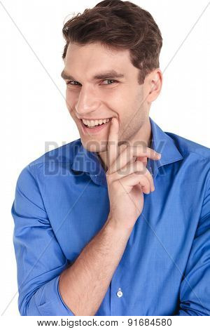 Happy young fashion man smiling at the camera while holding one finger to his mouth.