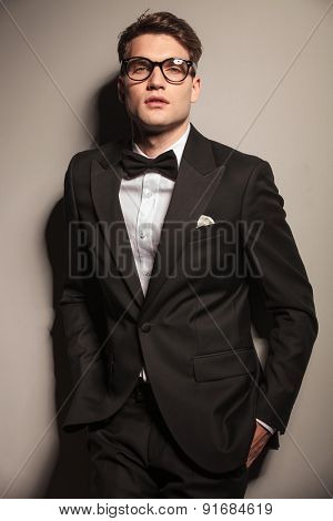 Young elegant business man posing on grey studio background with his hands in pockets.