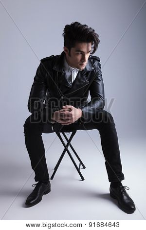 Full body picture of a young fashion man sitting on a stool while holding his hand together.
