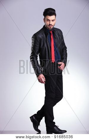 Casual business man walking on grey studio background while holding his belt.
