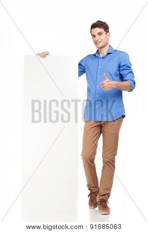Full body picture of a young fashion man holding a empty board while showing the thumbs up gesture.