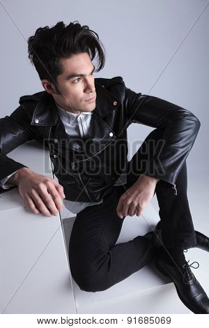 Up view of a handsome young man relaxing with his legs crossed, looking away from the camera.