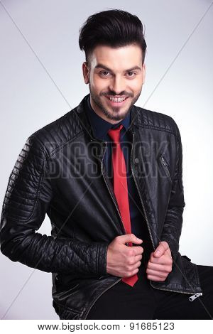 Happy young business man pulling his jacket while smiling at the camera.