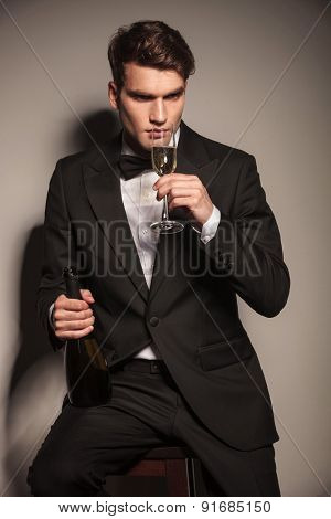 Handsome elegant business man sitting while drinking a glass of champagne