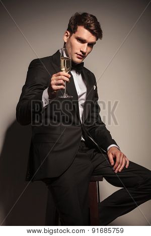 Handsome elegant business man offering you a glass of champagne while sitting on a chair.