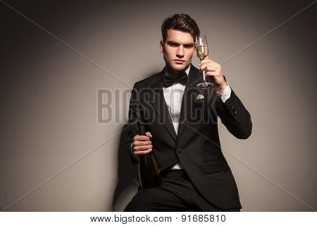 Elegant business man sitting while holding a bottle and a glass of champagne.