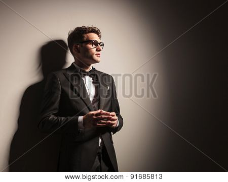Portrait of a young business man holding his hands together while leaning on a grey wall.