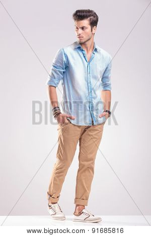 Casual young man walking on grey studio background with his hands in pockets, looking away from the camera.