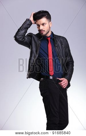 Side view of a handsome casual business man fixing his hair while holding his belt.