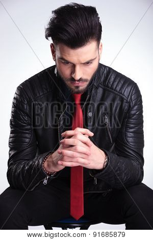 Close up picture of a casual business man sitting on a chair looking down while holding his hands together, thinking.