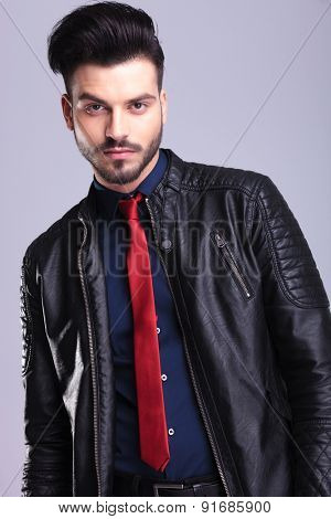 Portrait of a young casual business man wearing a leather jacket on grey studio background.