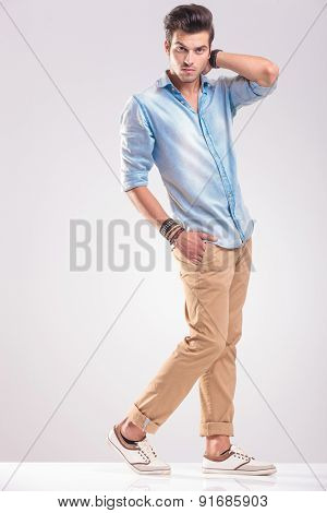 Handsome young casual man holding his hand to his neck while walking on studio background.