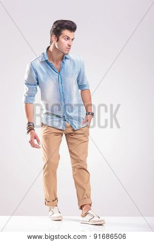 Picture of a young casual man holding one hand in his pocket while looking away.