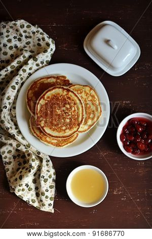 Pancakes On A White Plate With Honey And Jam On A Dark Wood Surface