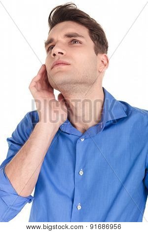 Close up picture of a handsome young man looking up while holdint one hand on his cheeckbone.