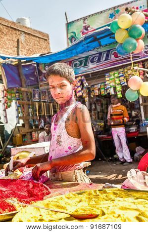 Little Boy With A Painted Face Selling Paint Colors For The Holi Festival In India