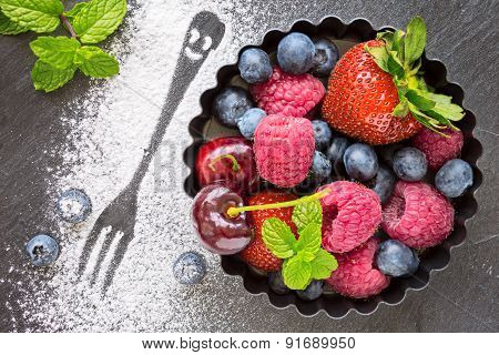 Mix Of Fresh Berries In A Small Round Metal Backing Mold And Sugar Print Of Fork, On Stone Gray Back