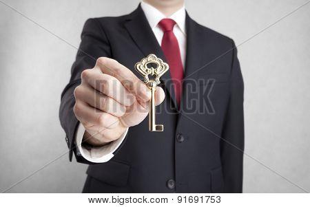 Golden key in businessman hand with clipping path