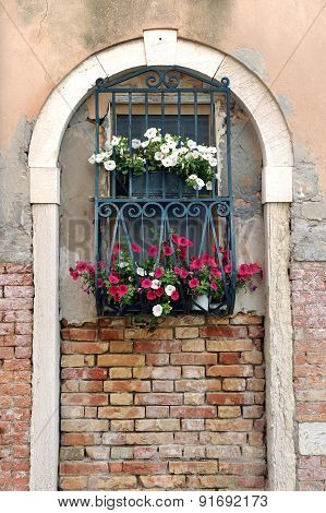 Window In Arch With Iron Bars And Flower Boxes