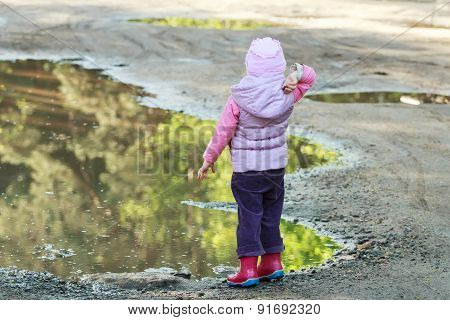 Toddler girl throwing pebbles into big summer puddle