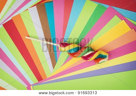 Colorful Twisted Sweet Lollipop And Brightly Colored Papers Background