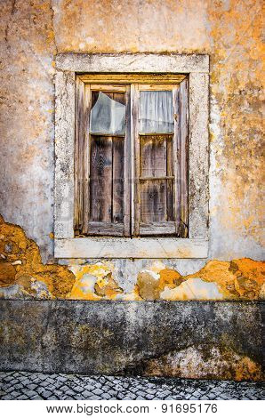 Detail of a broken window in an old yellow house ruin