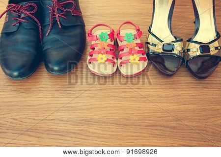 Three pairs of shoes: men, women and children. Shoes parents  and daughters.
