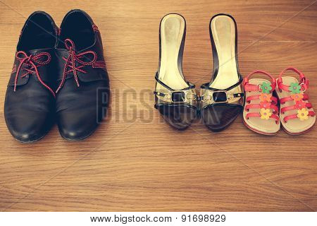 Three pairs of shoes: men, women and children. Baby sandals stand next to women's shoes.