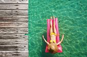 image of mattress  - Woman relaxing on inflatable mattress at the beach - JPG