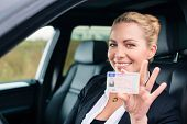 pic of driving  - Woman showing her driving license out of car window - JPG
