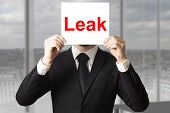 stock photo of leak  - businessman in black suit hiding face behind sign leak - JPG