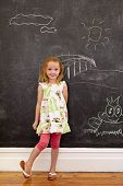 picture of innocence  - Full length portrait of innocent little girl standing at home looking at camera against a black wall with chalk drawings - JPG