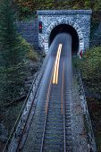 image of tunnel  - Old brick tunnel in the mountains and incoming train with long exposure - JPG