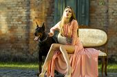 picture of thoroughbred  - Cute young woman with thoroughbred mastiff sitting on sofa near brick wall building looking away in long peach evening dress outdoor copyspace horizontal picture - JPG