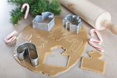 stock photo of christmas cookie  - rolled dough with christmas themed cookie cutters and rolling pin candy canes and christmas tree branches in the background christmas or new year time concept - JPG