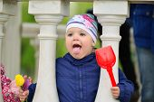 stock photo of taint  - Two year old girl looks out from the gazebo - JPG