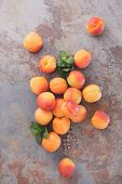 stock photo of apricot  - Still life of fresh apricots on a rustic stone surface - JPG