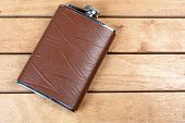 stock photo of flask  - Brown hip flask on the wooden table  - JPG