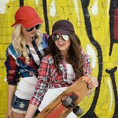 stock photo of skate board  - Two teen girl friends having fun together with skate board - JPG