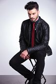 image of down jacket  - Young casual business man looking down while resting on a chair - JPG