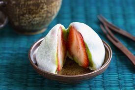 stock photo of fillies  - Daifuku with strawberry and green tea filliing by a cup of tea